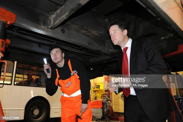 Deputy Prime Minister Nick Clegg inspects the underside of a bus with apprentice Jack Maybury during a visit to National Express West Midlands...
