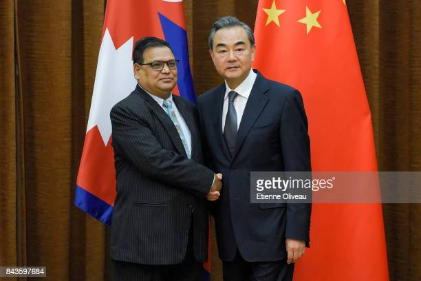 Deputy Prime Minister Of Nepal Krishna Bahadur Mahara shakes hands with Chinese Foreign Minister Wang Yi as he arrives for a meeting at the Ministry...