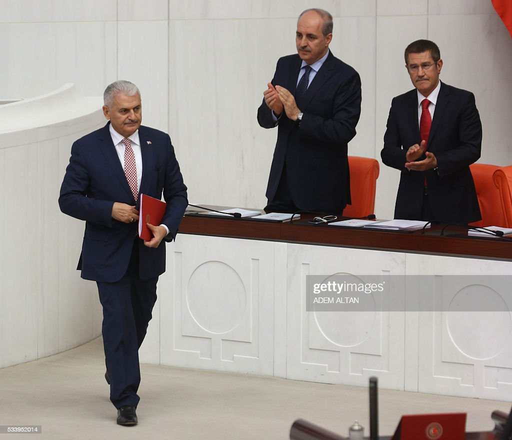 Deputy Prime Ministers Nurettin Canikli (R) and Numan Kurtulmus (2nd R) applaud as the Turkish Prime Minister Binali Yildirim (L) walks past before presenting Turkeys 65th government's program to the Grand National Assembly of Turkey (TBMM) in Ankara, on May 24, 2016. / AFP / ADEM
