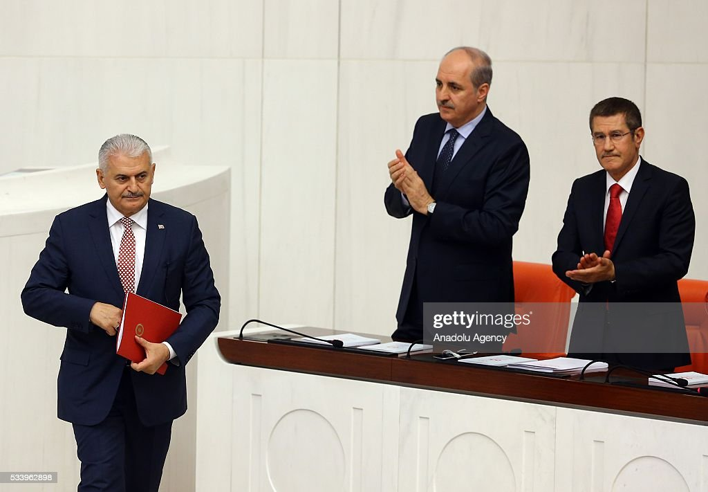 Deputy Prime Ministers Nurettin Canikli (R) and Numan Kurtulmus (2nd R) applaud as the Turkish Prime Minister Binali Yildirim (L) walks past before presenting the Turkeys 65th government's program to the Grand National Assembly of Turkey (TBMM) in Ankara, Turkey on May 24, 2016.
