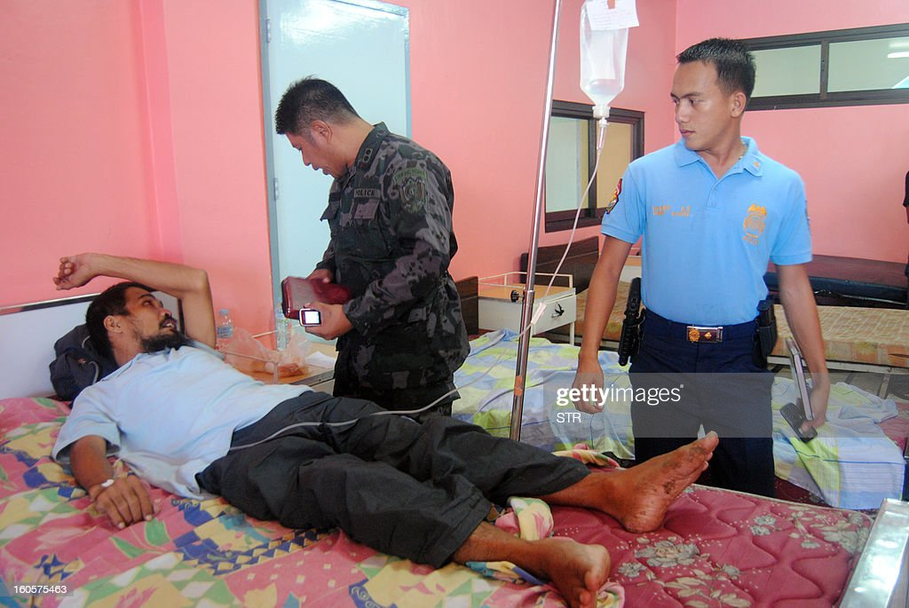 Deputy provincial police chief Roy Gabor (2nd R) interviews freed Philippine hostage, cameraman Ramil Vela as he recuperates at the provincial hospital in Jolo, Sulu province, in the southern island of Mindanao on February 3, 2013, hours after Vela and a colleague walked free from Islamist Abu Sayyaf militants. Islamist Abu Sayyaf militants have freed two Filipino television crew members seized along with a Jordanian journalist nearly eight months ago in the southern Philippines, police said February 3.