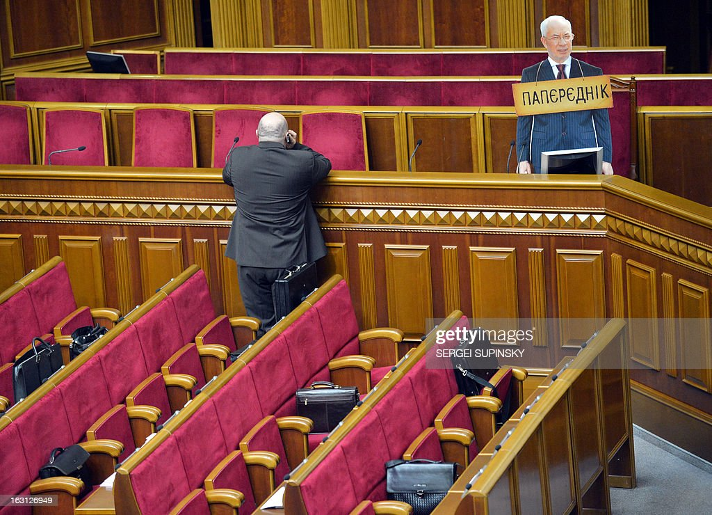 A deputy speaks on the phone near a cardboard cut-out of Ukrainian Prime Minister Mykola Azarov with a placard around the neck reading 'Predecessor' standing nearby after it was set up by the Ukrainian parliamentary opposition as they tried to block the speaker's platform on March 5, 2013 during a session of parliament in Kiev. The deputies were trying to prevent an initiative by the majority to deprive deputy of the opposition and lawyer of jailed the former Prime Minister Yulia Tymoshenko, Sergiy Vlasenko, of his deputative powers and status.