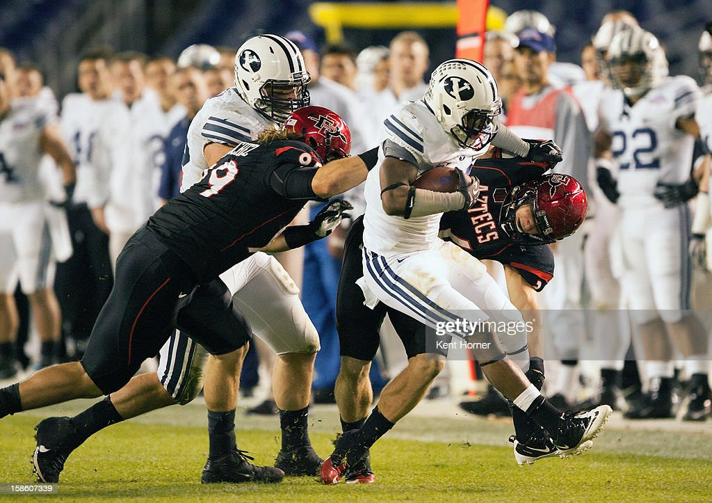 DeQuan Everett #21 of the BYU Cougars runs with the ball in the first half of the game as Rene Siluano #39 and Hunter Hewitt #89 of the San Diego State Aztecs tackle in the Poinsettia Bowl at Qualcomm Stadium on December 20, 2012 in San Diego, California.