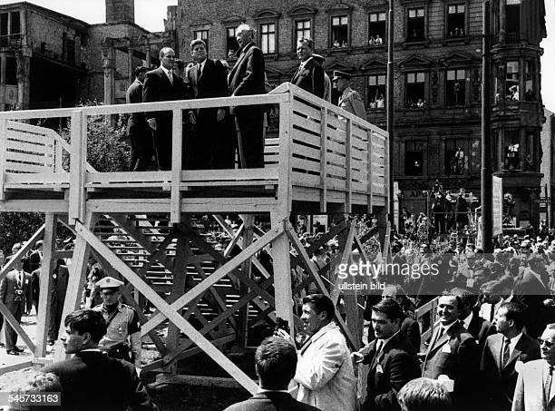 Der amerikanische Präsident John FKennedy auf einemBeobachtungsstand am Checkpoint Charlierechts neben ihm Bundeskanzler KonradAdenauer und der...