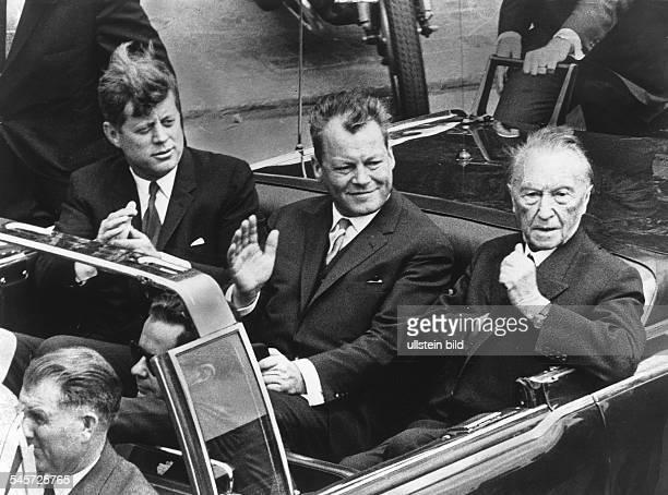 Der amerikanische Präsident John FKennedy während der Fahrt im offenenWagen durch die Stadt vlnrKennedy der Regierende BürgermeisterWilly Brandt und...