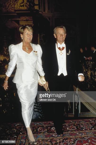 Der deutsche Verleger Gustav Heinrich Lübbe im Abendanzug geht neben seiner Frau Ursula die ein weißes glänzendes Kleid trägt Beide tragen einen...