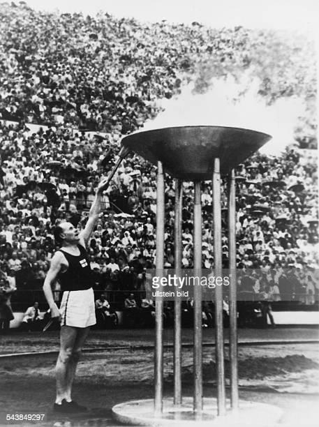 Der finnische Langstreckenläufer Paavo Nurmi entzündet 1952 bei den Olympischen Sommerspielen in Helsinki das Olympische Feuer Im Hintergrund...