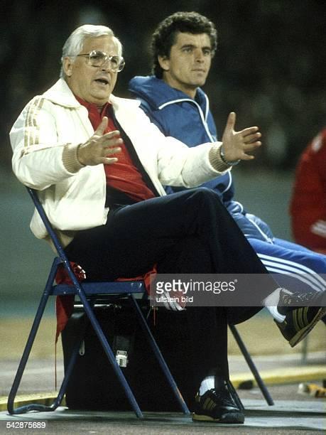 Der Fußballbundestrainer Jupp Derwall sitzt während des Länderspiels Deutschland gegen Wales in Köln mit übereinander geschlagenen Beinen und...
