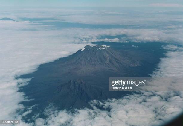 Der Kilimanjaro erhebt sich aus einem Wolkenmeer Auf den Gipfeln sind Schneefelder zu sehen
