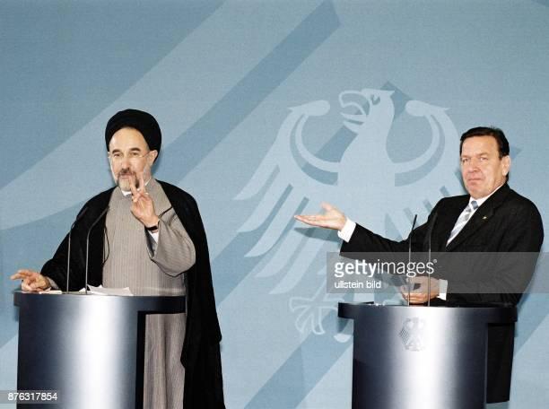 Der Präsident des Iran Mohammed Khatami neben dem Bundeskanzler der BRD Gerhard Schröder Beide stehen an Rednerpulten auf denen Mikrofone zu sehen...