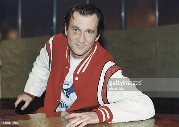 Der Schauspieler Peter Lohmeyer sitzt in einer rotweißen Jacke und TShirt mit halbverdecktem Aufdruck des Fußballvereins 'FC Schalke 04' an einem...