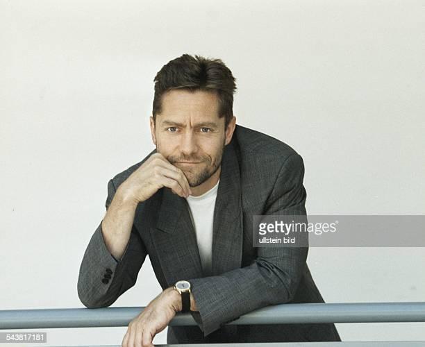 Der Schauspieler Udo Schenk lehnt an einem Geländer Er trägt eine graue Jacke mit weißem TShirt am Handgelenk eine Armbanduhr Aufgenommen August 1997