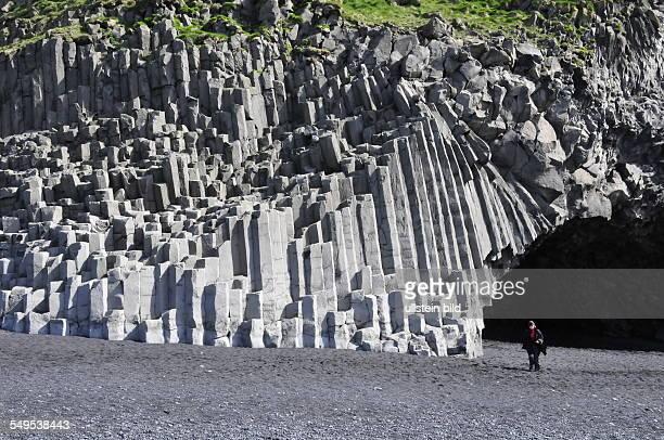 Der schwarze Vulkansandstrand die Basaltsäulenformationen unterhalb des Berges Reynisfjall und die Höhle Halsanefshellir in einem Strandabschnitt am...