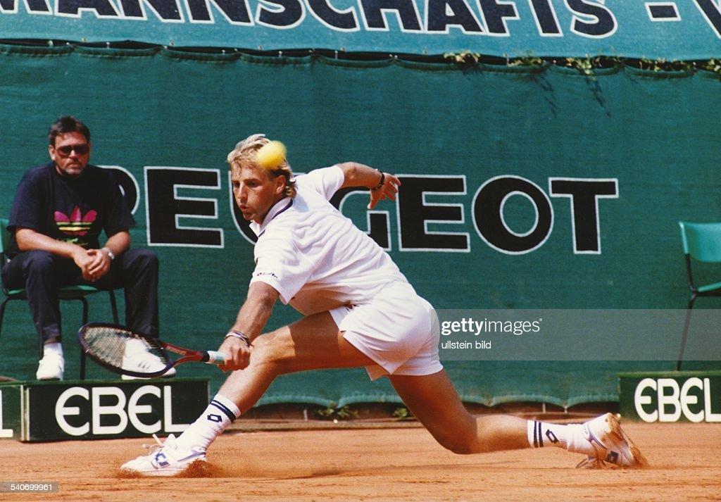 Der österreichische Tennisspieler Thomas Muster rutscht über den Sandplatz, um an der Grundlinie den Ball zu erreichen. Im Hintergrund sitzt der Linienrichter auf seinem Stuhl. Aufgenommen Mai 1990.