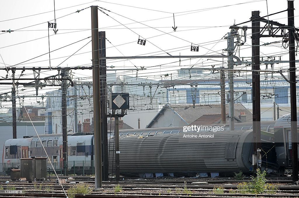 A derailed carriage lies across tracks the day following a train accident at Bretigny-sur-Orge railway station on July 13, 2013 in Bretigny-sur-Orge, France. An intercity train carrying 385 passengers, travelling from Paris towards Limoges, derailed crashing into a station platform leaving six people dead and a further 26 injured. French investigators for SNCF have stated that the cause by a fault in the tracks.