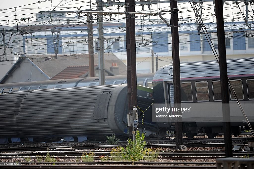 Derailed carriages lie across rail tracks the day following a train accident at Bretigny-sur-Orge railway station on July 13, 2013 in Bretigny-sur-Orge, France. An intercity train carrying 385 passengers, travelling from Paris towards Limoges, derailed crashing into a station platform leaving six people dead and a further 26 injured. French investigators for SNCF have stated that the cause by a fault in the tracks.