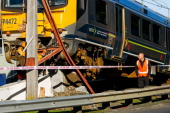 A derailed commuter train rests at the end of the line at Melling Station as a worker assesses the damage on May 27 2014 in Wellington New Zealand...