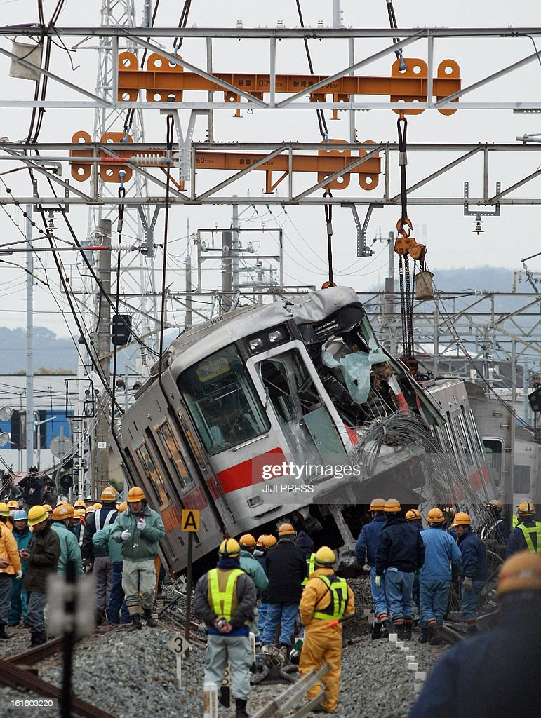 A derailed passenger train of the Sanyo Electric Railway is lifted by a crane, one day after the train hit a truck at a level crossing in Takasago city in Hyogo prefecture, western Japan on February 13, 2013. Sixteen people were injured in a collision and a driver of the train was seriously. AFP PHOTO / JIJI PRESS JAPAN OUT