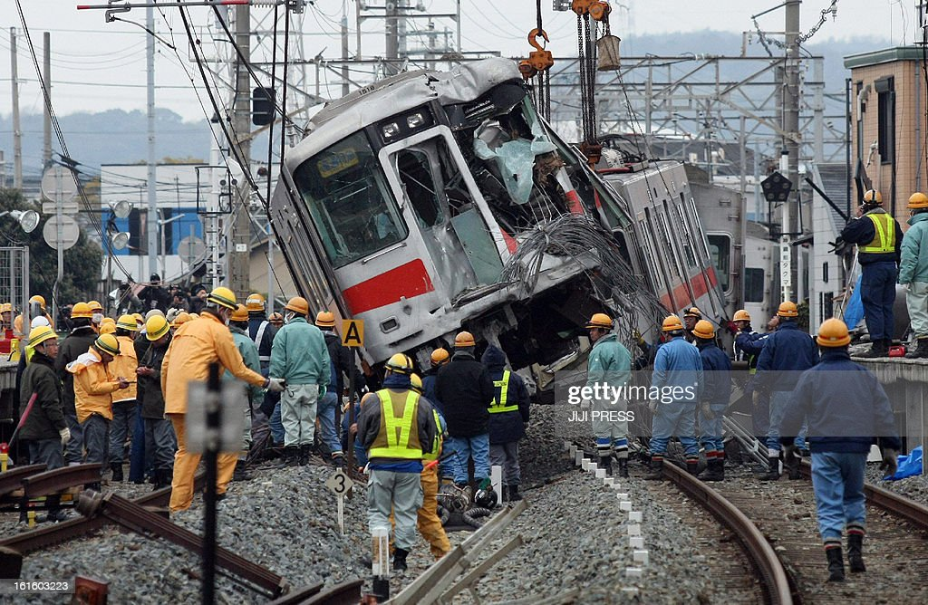 A derailed passenger train of the Sanyo Electric Railway is lifted by a crane, one day after the train hit a truck at a level crossing in Takasago city in Hyogo prefecture, western Japan on February 13, 2013. Sixteen people were injured in a collision and a driver of the train was seriously.