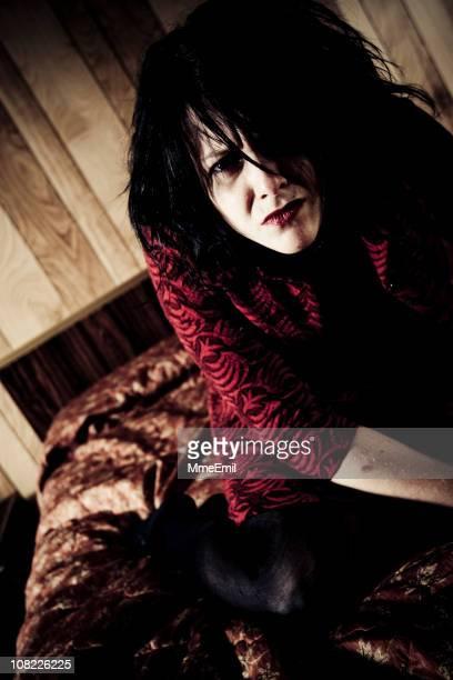 Deranged Junge Frau sitzt auf dem Bett