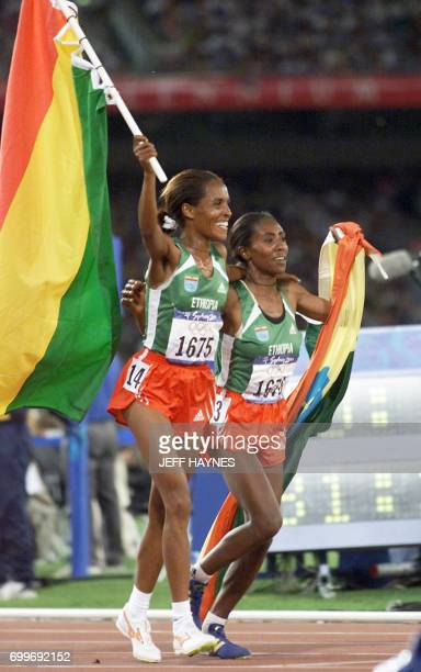 Derartu Tulu of Ethiopia and compatriot Gete Wami display the Ehtiopian flag during the lap of honor 30 September 2000 at the Sydney Olympic Games...