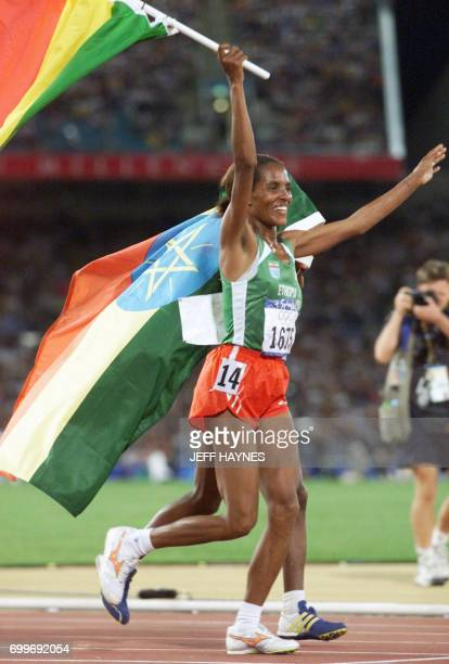 Derartu Tulu of Ethiopia flanked by compatriot Gete Wami flashes a big smile 30 September 2000 at the Sydney Olympic Games after respectively winning...