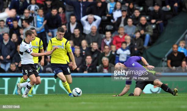 Derby County's Craig Bryson and Birmingham City's Callum Reilly battle for the ball as referee Roger East slips over during the Sky Bet Championship...