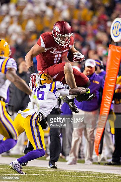 Derby of the Arkansas Razorbacks jumps over Tre'Davious White of the LSU Tigers during the second quarter at Razorback Stadium on November 15 2014 in...