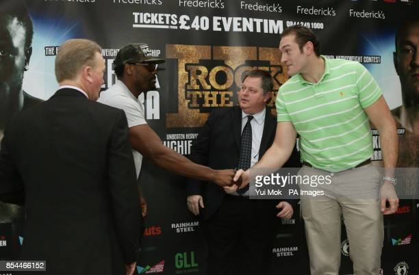 Dereck Chisora shakes hands with Tyson Fury as promoters Mick Hennessy and Frank Warren look on during the press conference at Fredericks Restaurant...