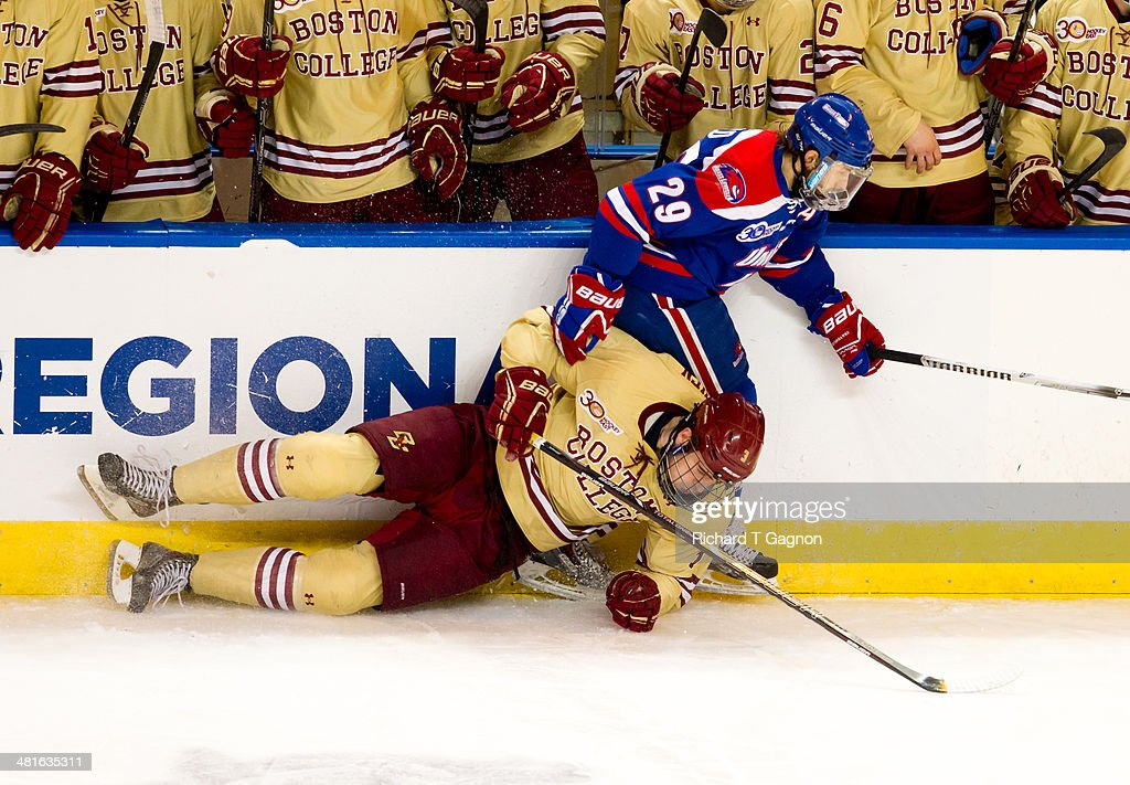 Derek Arnold #29 of the Massachusetts Lowell River Hawks and Ian McCoshen #3 of the Boston College Eagles hit the boards during the NCAA Division I Men's Ice Hockey Northeast Regional Championship Final at the DCU Center on March 30, 2014 in Worcester, Massachusetts.