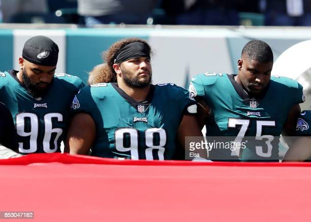 Derek Barnett Elijah Qualls and Vinny Curry of the Philadelphia Eagles link arms during the national anthem before the game against the New York...