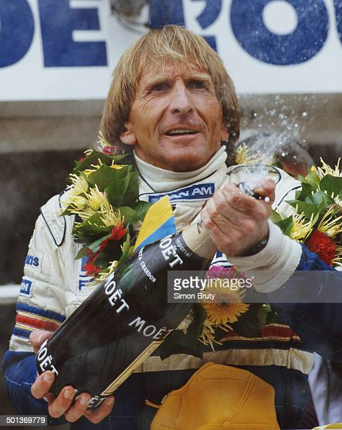 Derek Bell of Great Britain and drive of the Rothmans Porsche AG Porsche 962C sprays champagne as he celebrates winning the FIA World Sportscar...