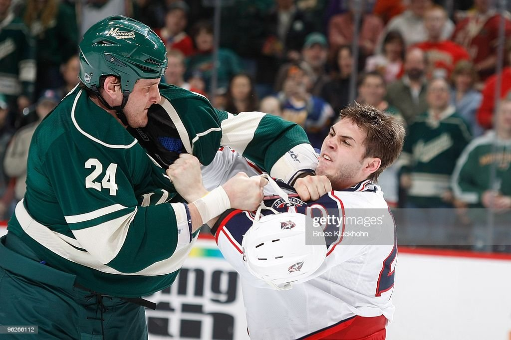 Derek Boogaard of the Minnesota Wild fights with Jared Boll of the Columbus Blue Jackets during the game at the Xcel Energy Center on January 23 2010...