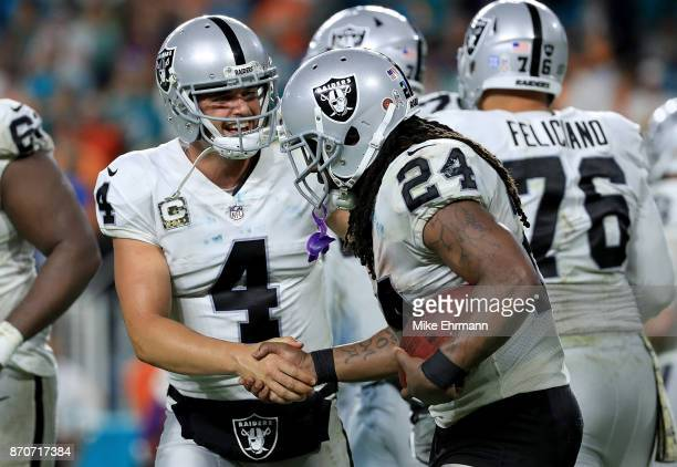 Derek Carr and Marshawn Lynch of the Oakland Raiders celebrate a touchdown during a game against the Miami Dolphins at Hard Rock Stadium on November...