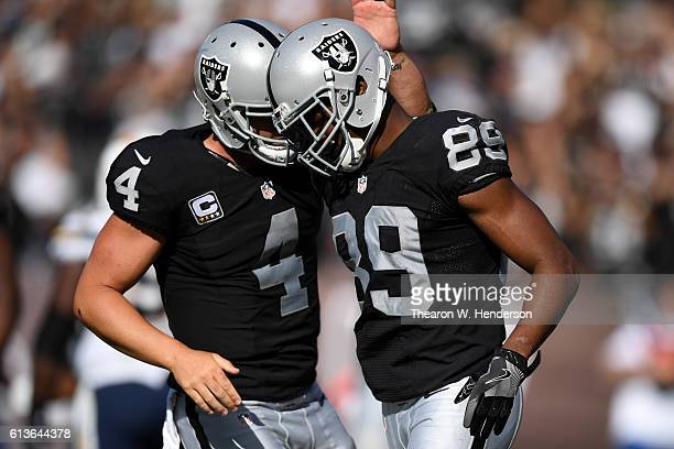 Derek Carr of the Oakland Raiders celebrates with Amari Cooper after a scoring on a twopoint conversion against the San Diego Chargers during their...