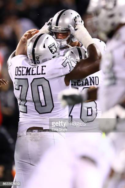 Derek Carr of the Oakland Raiders celebrates with Kelechi Osemele after defeating the Kansas City Chiefs 3130 in their NFL game at OaklandAlameda...