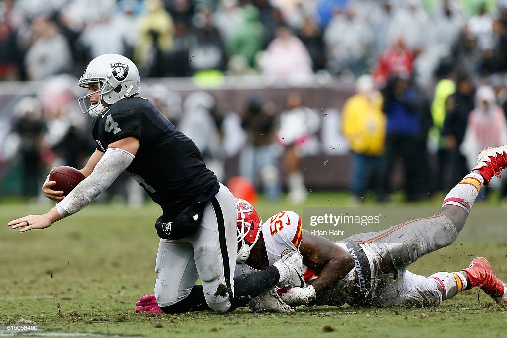 Derek Carr #4 of the Oakland Raiders is sacked by Dee Ford #55 of the Kansas City Chiefs during their NFL game at Oakland-Alameda County Coliseum on October 16, 2016 in Oakland, California.