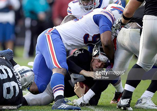 Derek Carr of the Oakland Raiders is sacked by Mario Williams of the Buffalo Bills at Oco Coliseum on December 21 2014 in Oakland California