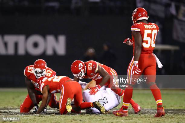 Derek Carr of the Oakland Raiders lays on the field after a late hit by Marcus Peters of the Kansas City Chiefs during their NFL game at...