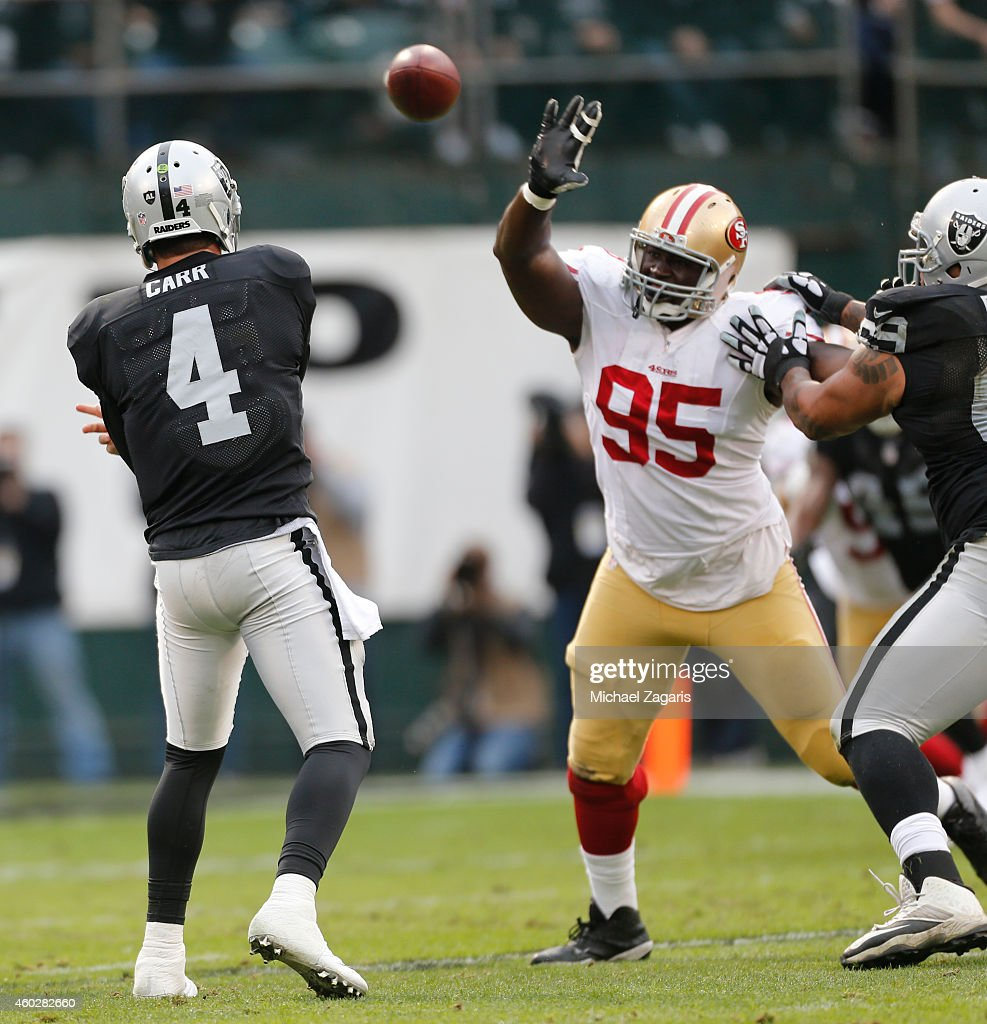 <a gi-track='captionPersonalityLinkClicked' href=/galleries/search?phrase=Derek+Carr&family=editorial&specificpeople=8222798 ng-click='$event.stopPropagation()'>Derek Carr</a> #4 of the Oakland Raiders passes under pressure by <a gi-track='captionPersonalityLinkClicked' href=/galleries/search?phrase=Tank+Carradine&family=editorial&specificpeople=10915724 ng-click='$event.stopPropagation()'>Tank Carradine</a> #95 of the San Francisco 49ers during the game at O.co Coliseum on December 7, 2014 in Oakland, California. The Raiders defeated the 49ers 24-13.