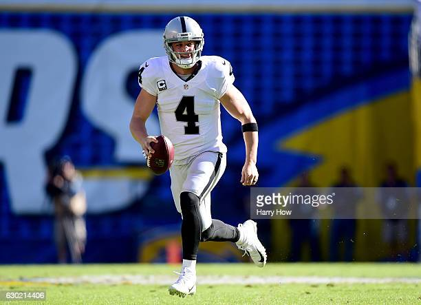 Derek Carr of the Oakland Raiders scrambles out of the pocket for a first down during the first quarter against the San Diego Chargers at Qualcomm...
