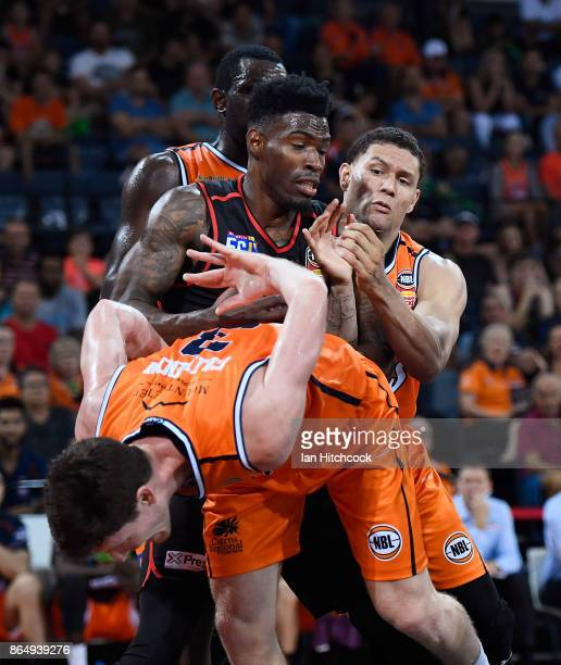 Derek Cooke Jr of the Wildcats contests the ball with Michael Carrera and Cam Gliddon of the Taipans during the round three NBL match between the...