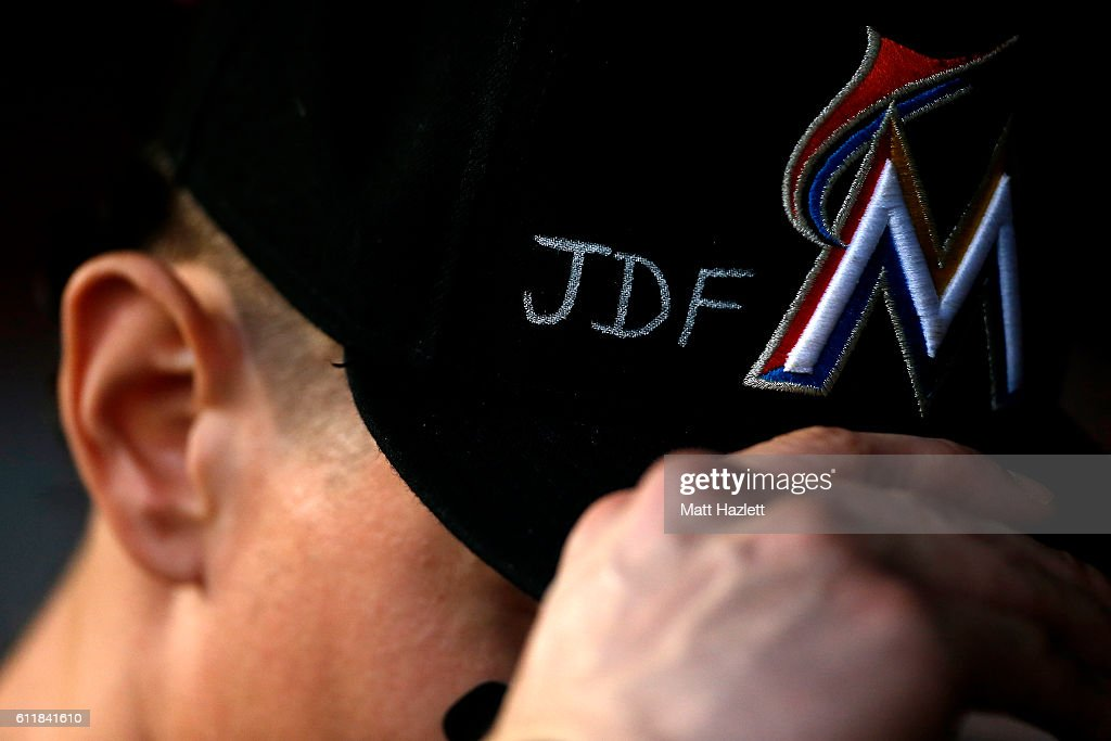 Derek Dietrich #32 of the Miami Marlins adjusts his hat which displays support for Miami Marlins pitcher Jose Fernandez, who died in a boating accident, in the third inning against the Washington Nationals at Nationals Park on October 1, 2016 in Washington, DC.