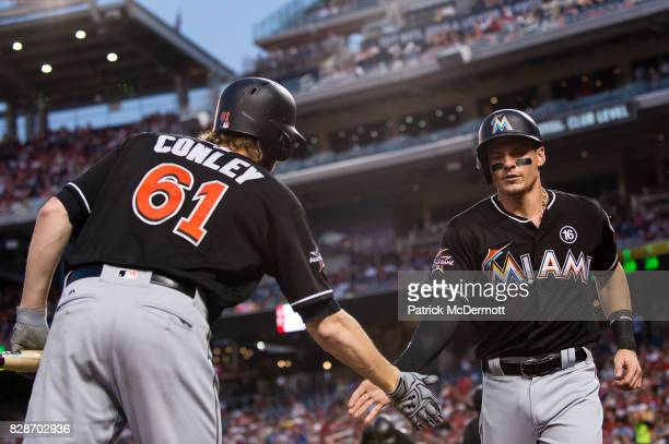 Derek Dietrich of the Miami Marlins celebrates with Adam Conley after scoring a run on a RBI single hit by Ichiro Suzuki in the fourth inning during...