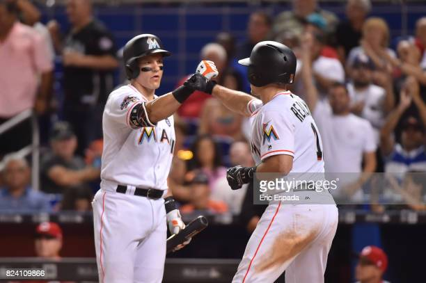Derek Dietrich of the Miami Marlins congratulates JT Realmuto after hitting a home run against the Cincinnati Reds at Marlins Park on July 28 2017 in...