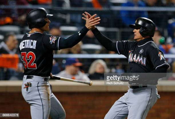 Derek Dietrich of the Miami Marlins congratulates Miguel Rojas after both scored on a double off the bat of Dee Gordon in the third inning of a game...