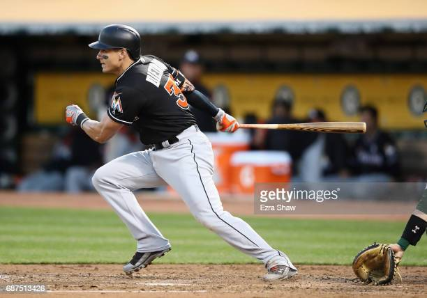 Derek Dietrich of the Miami Marlins hits a single that scored a run in the third inning against the Oakland Athletics at Oakland Alameda Coliseum on...
