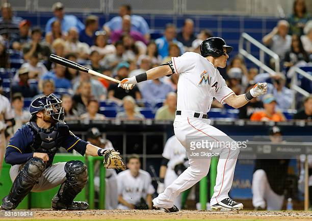 Derek Dietrich of the Miami Marlins hits an eighth inning single in front outfield Jonathan Lucroy of the Milwaukee Brewers at Marlins Park on May 11...