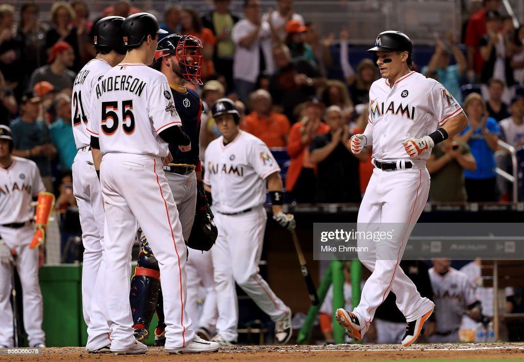 Derek Dietrich #32 of the Miami Marlins is congratulated by Christian Yelich #21 and Brian Anderson #55 after a three run home run in the first inning during a game against the Atlanta Braves at Marlins Park on September 30, 2017 in Miami, Florida.