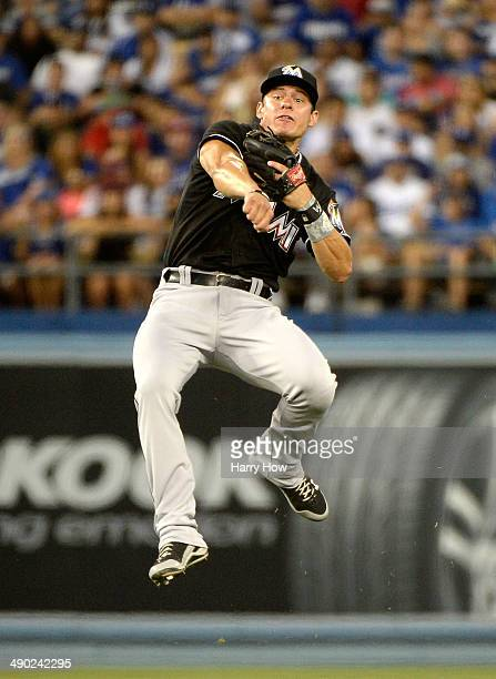 Derek Dietrich of the Miami Marlins reacts as he makes a throwing error to first base on a groundball from Josh Beckett of the Los Angeles Dodgers...